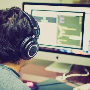 Un homme travaille à un ordinateur, en portant des casques audio