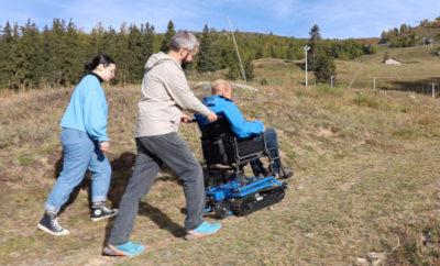 Trois personnes, dont une personne en fauteuil roulant testent sur un chemin de randonnée de l'utilisation du Freedom Trax