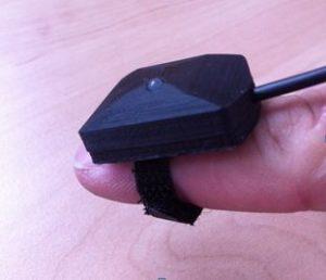 L'appareil noir est fixé sur le bout d'un doigt