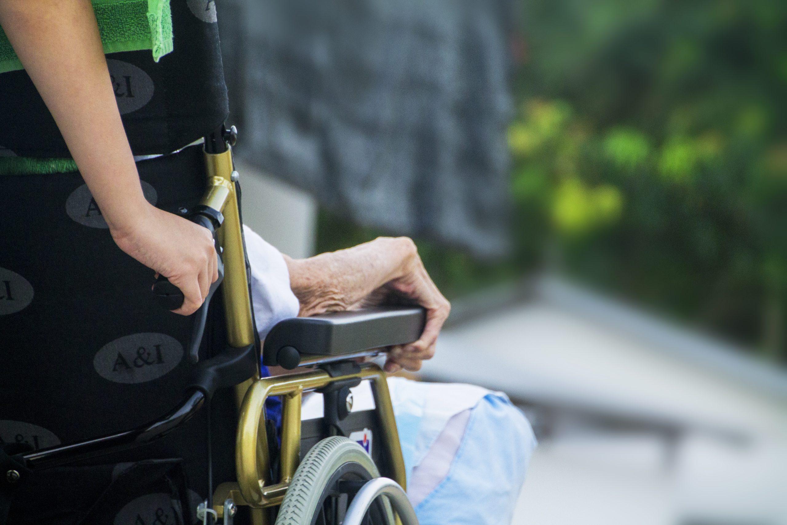 Une éducatrice accompagne une personne en fauteuil roulant.