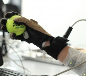 Une main qui porte un gant tient une balle de tennis. Le bras est monitoré et des informations apparaissent sur un écran d'ordinateur.