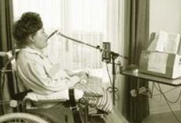 Une femme dans une chaise roulante utilise un appareil d'assistance, avec la bouche.