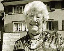 Une vielle femme sourit, devant une maison