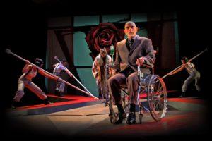 Sur une scène de théâtre, un comédien en chaise roulante regarde le public, devant quatre autres comédiens