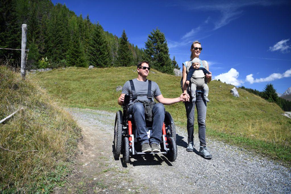 Un couple fait une randonnée en montagne, l'homme en chaise roulante tient la main de la femme qui porte le bébé devant elle