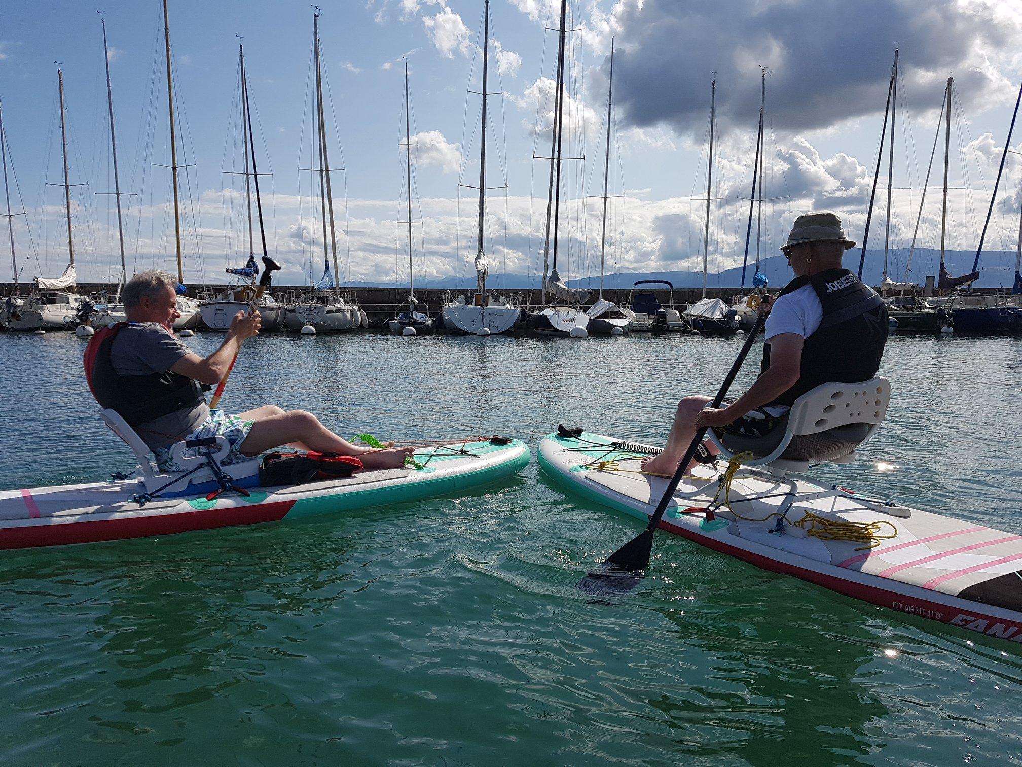 Zwei Menschen mit eingeschränkter Mobilität sitzen auf Brettern und segeln auf einem See
