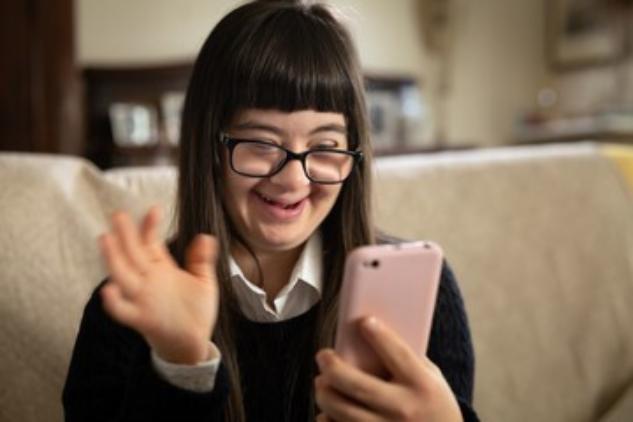 eine junge Frau mit Down-Syndrom nutzt ein Smartphone
